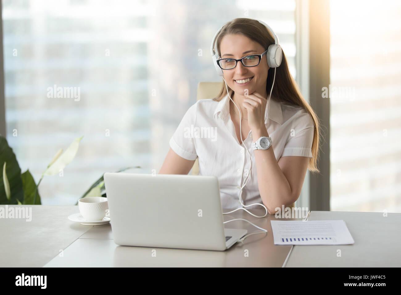 Sorridente imprenditrice che indossano le cuffie con il computer portatile in posa a w Immagini Stock