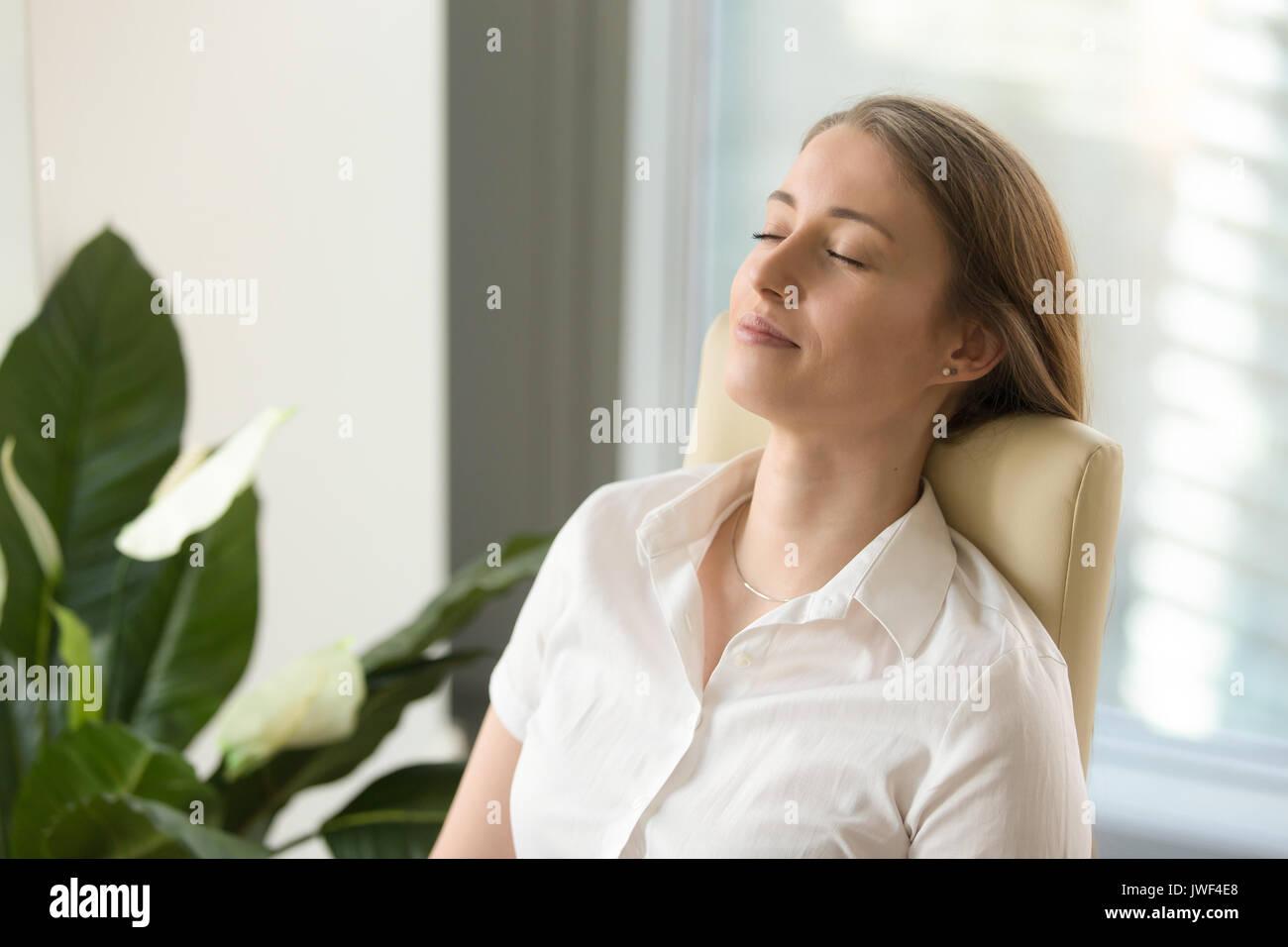 Calma e attraente donna rilassati Pendente ritornare su office cha Immagini Stock