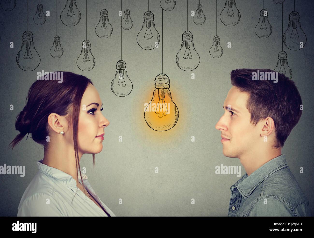 Abilità cognitive capacità concetto, maschio vs femmina. Uomo e donna che guarda la luce brillante lampadina isolato sul muro grigio sfondo Immagini Stock