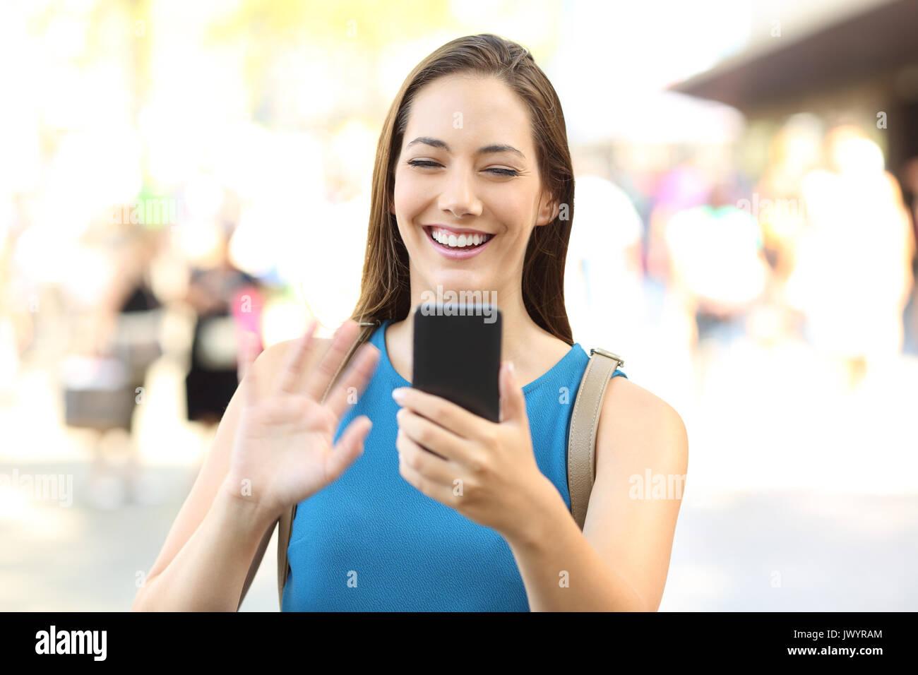 Felice lady saluto durante una chiamata video con uno smart phone su strada Immagini Stock