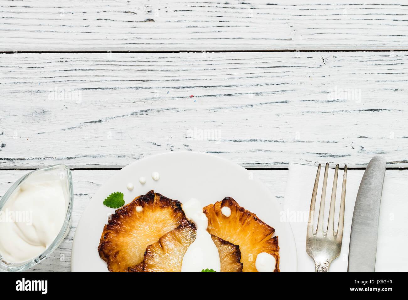 Frittura di fette di ananas con creme fraiche, menta nella piastra bianca su sfondo di legno. Vista superiore, spazio di copia Immagini Stock