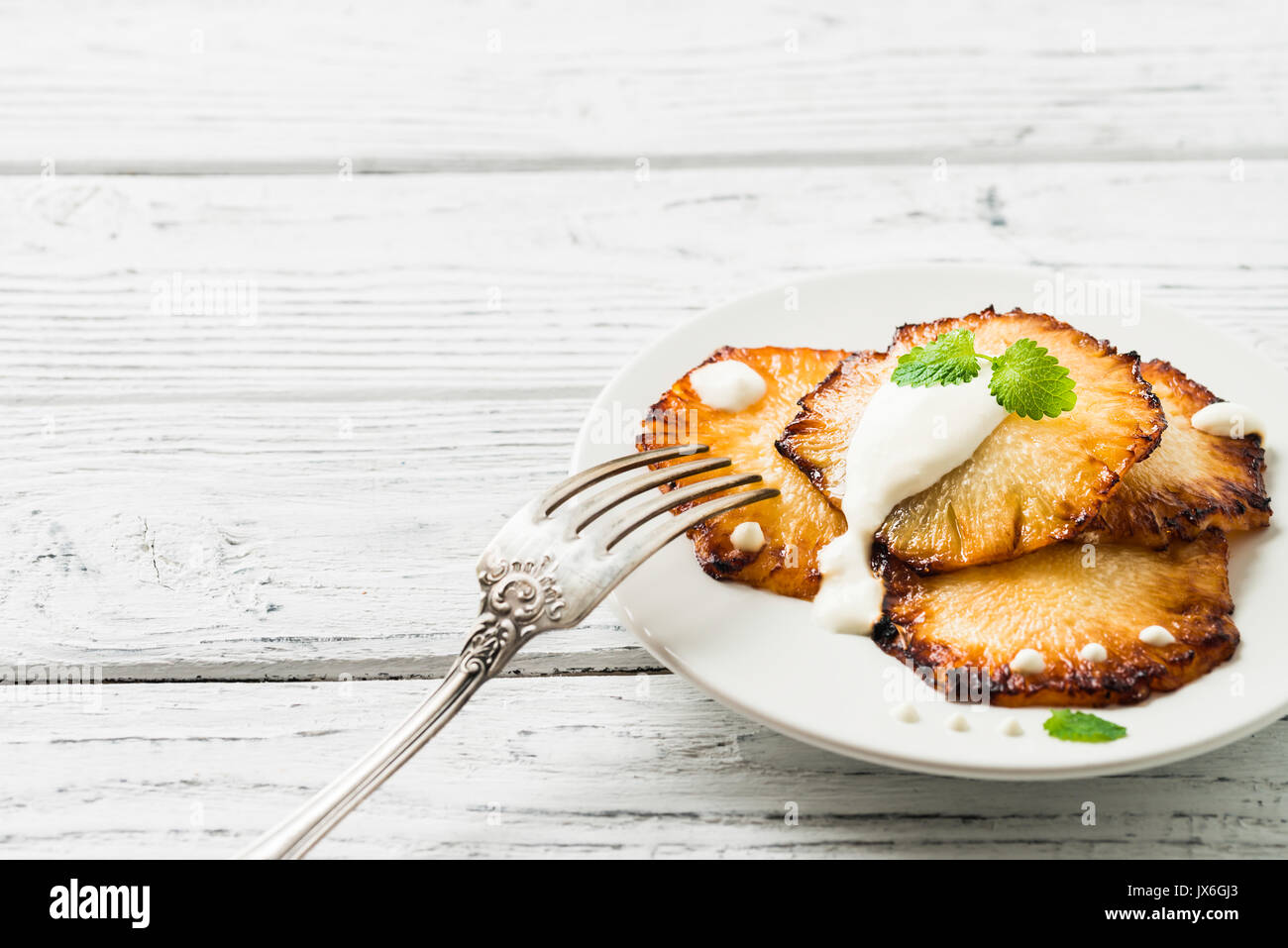 Frittura di fette di ananas con creme fraiche, menta nella piastra bianca su sfondo di legno. Spazio di copia Immagini Stock