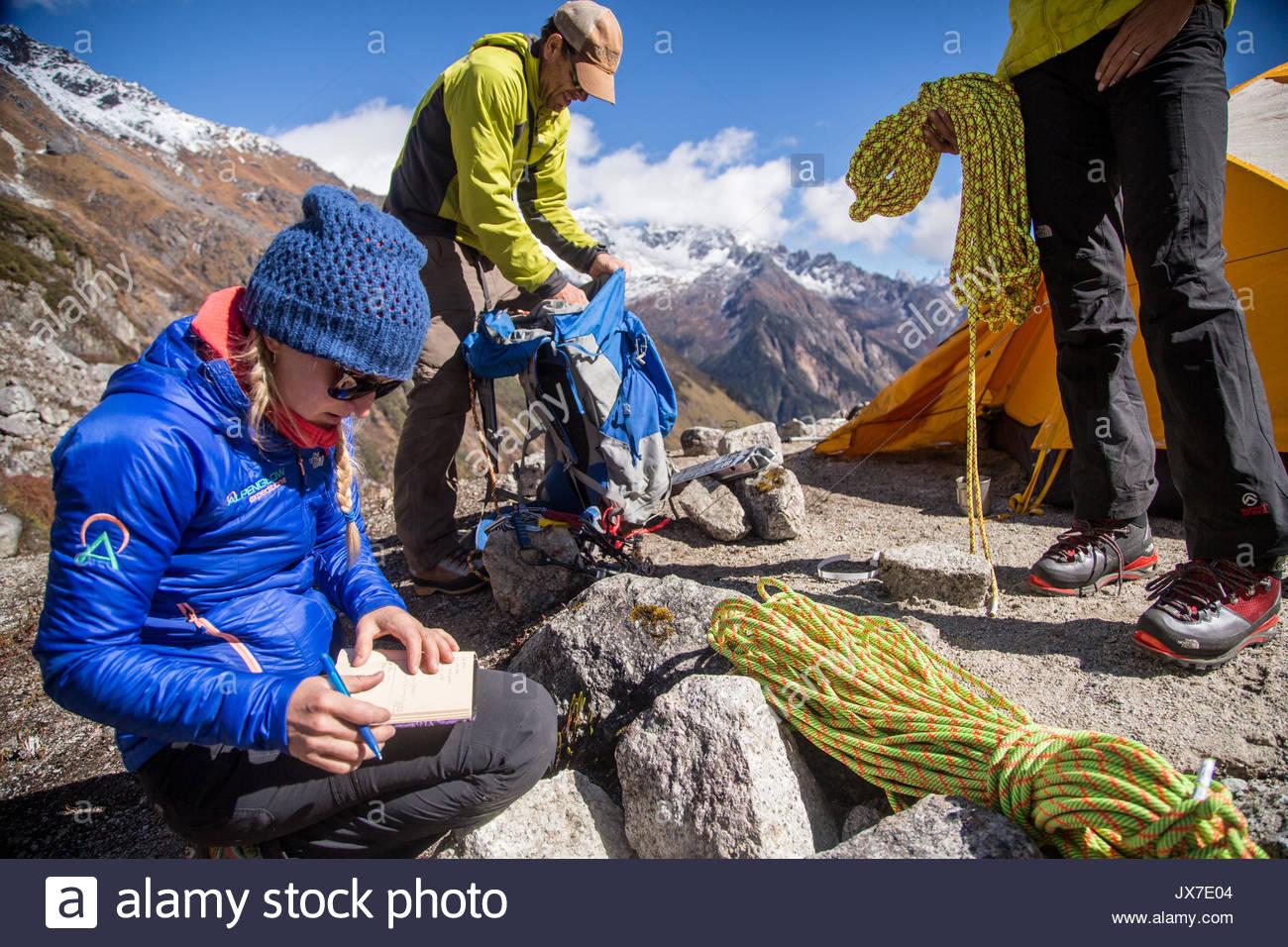 Membri della spedizione di ingranaggio di controllo e rivedere i piani prima di impostare l'alpinismo. Immagini Stock