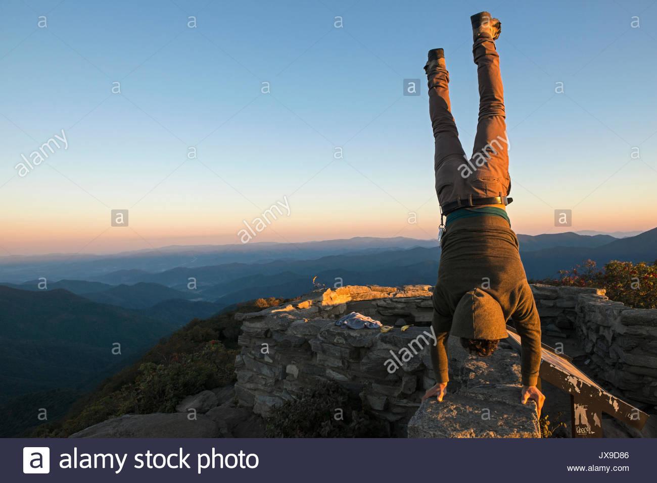Un uomo compie un handstand alla sommità del Pinnacle scoscese sentiero lungo la Blue Ridge Parkway. Immagini Stock
