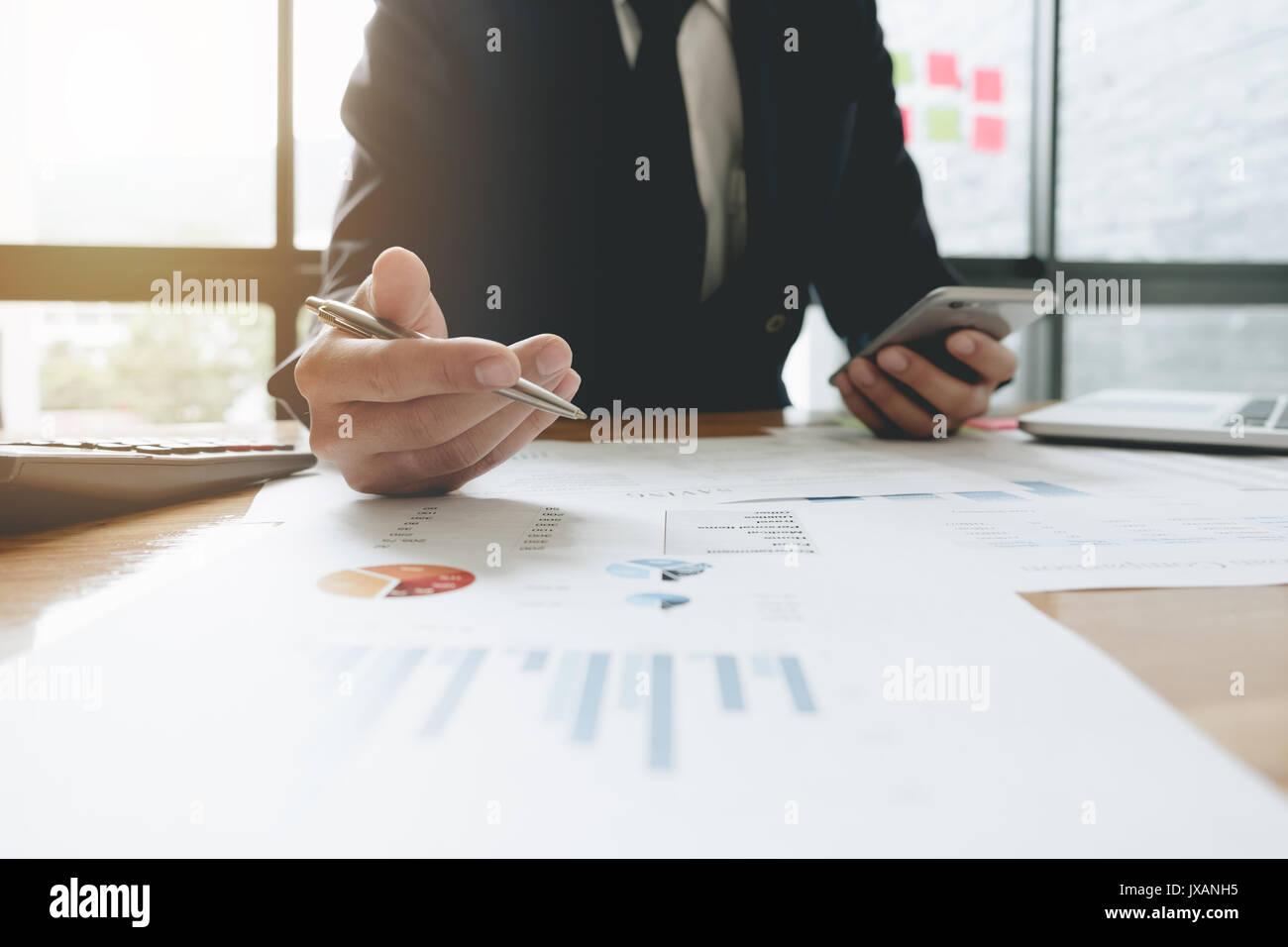 Uomo d'affari consulente per gli investimenti della società di analisi la relazione finanziaria annuale bilancio dichiarazione di lavoro con documenti grafici. Concetto di immagine Immagini Stock