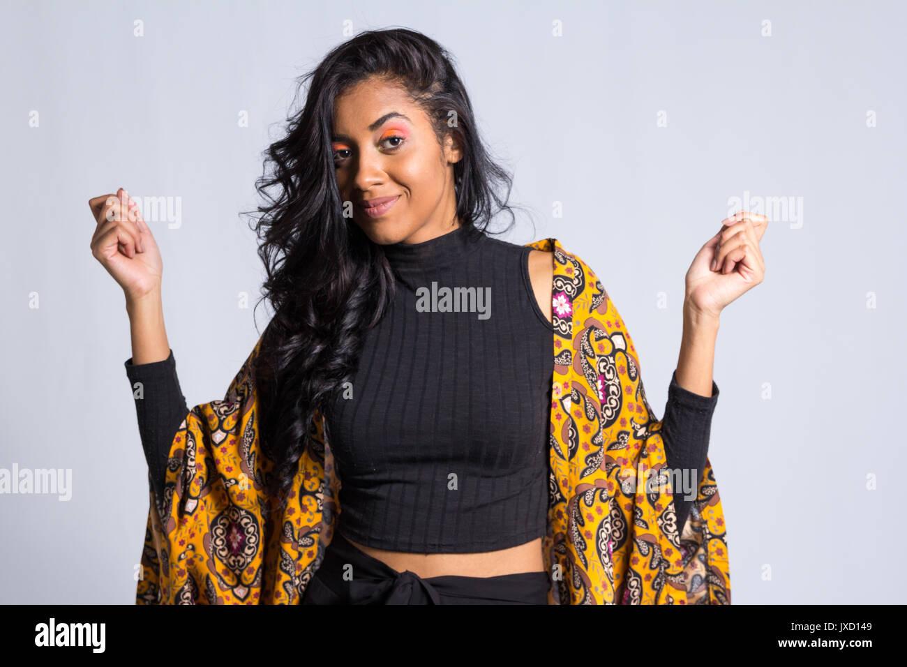 30310e2c29 Afrodescendant donna indossa nero e giallo abbigliamento. Lei è brasiliana.  Specchio colorato. Moda