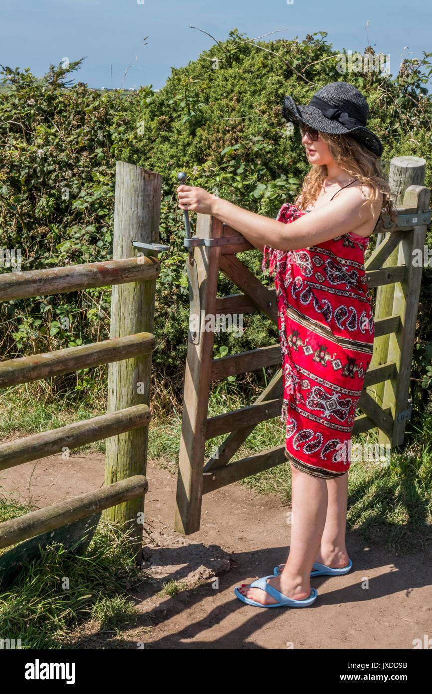 Una bella giovane donna, che indossa un sarong e hat, apertura a cinque bar porta ad un sentiero che conduce alla spiaggia di Gwynver, Cornwall, Inghilterra, Regno Unito. Immagini Stock