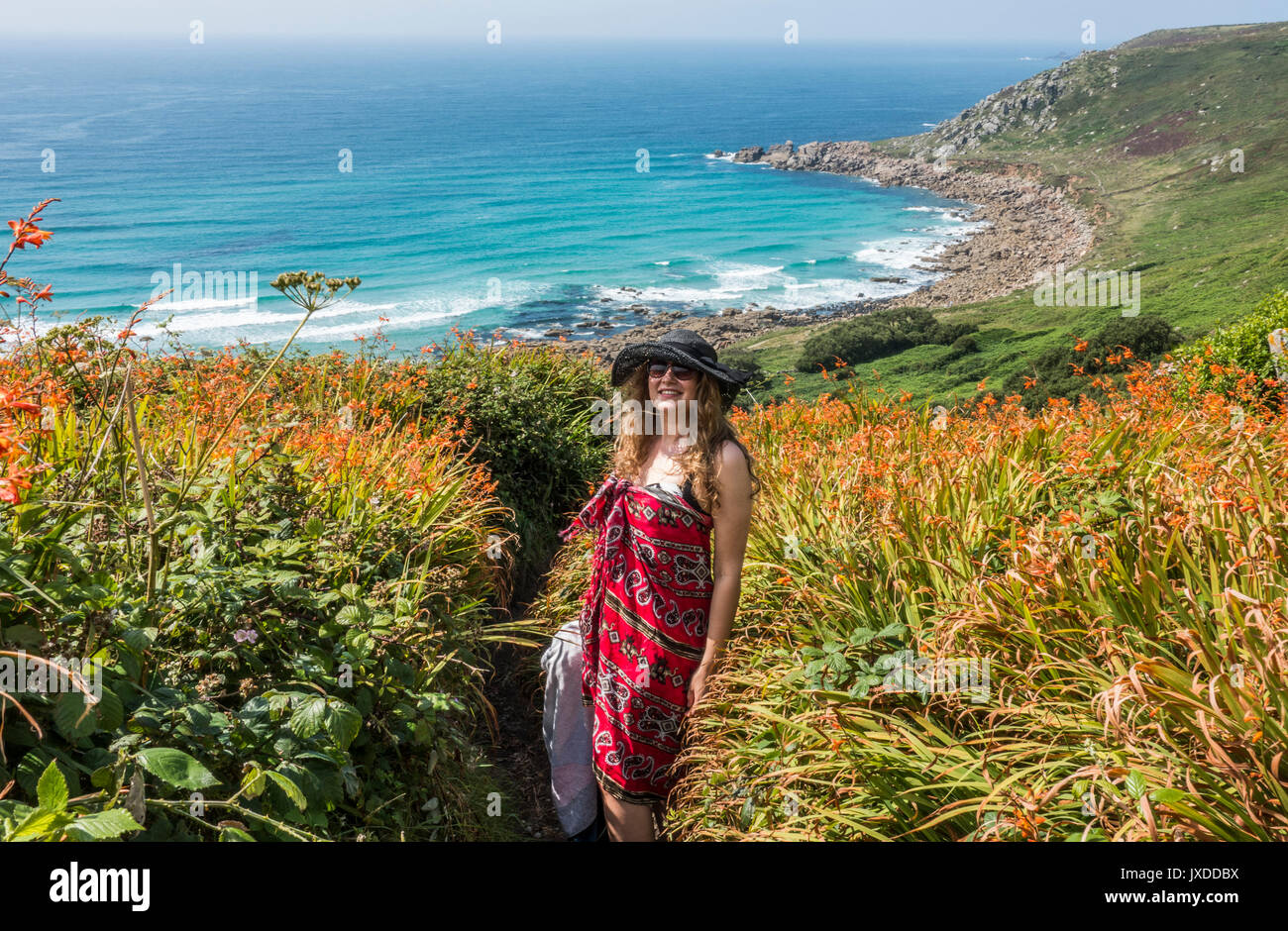 Una bella giovane donna, che indossa un sarong e hat, in piedi su uno stretto sentiero che conduce alla spiaggia di Gwynver, Cornwall, Inghilterra, Regno Unito. Immagini Stock