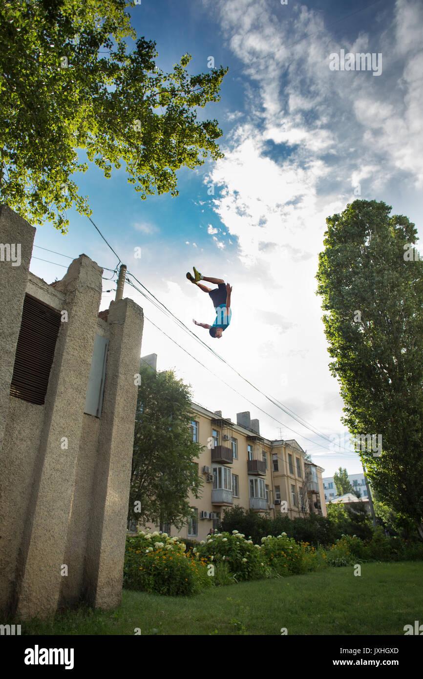 Città parkour. Il ragazzo non il contrario somersault. Scattare da un angolo basso. Agilità, adrenalina e extreme. Immagini Stock