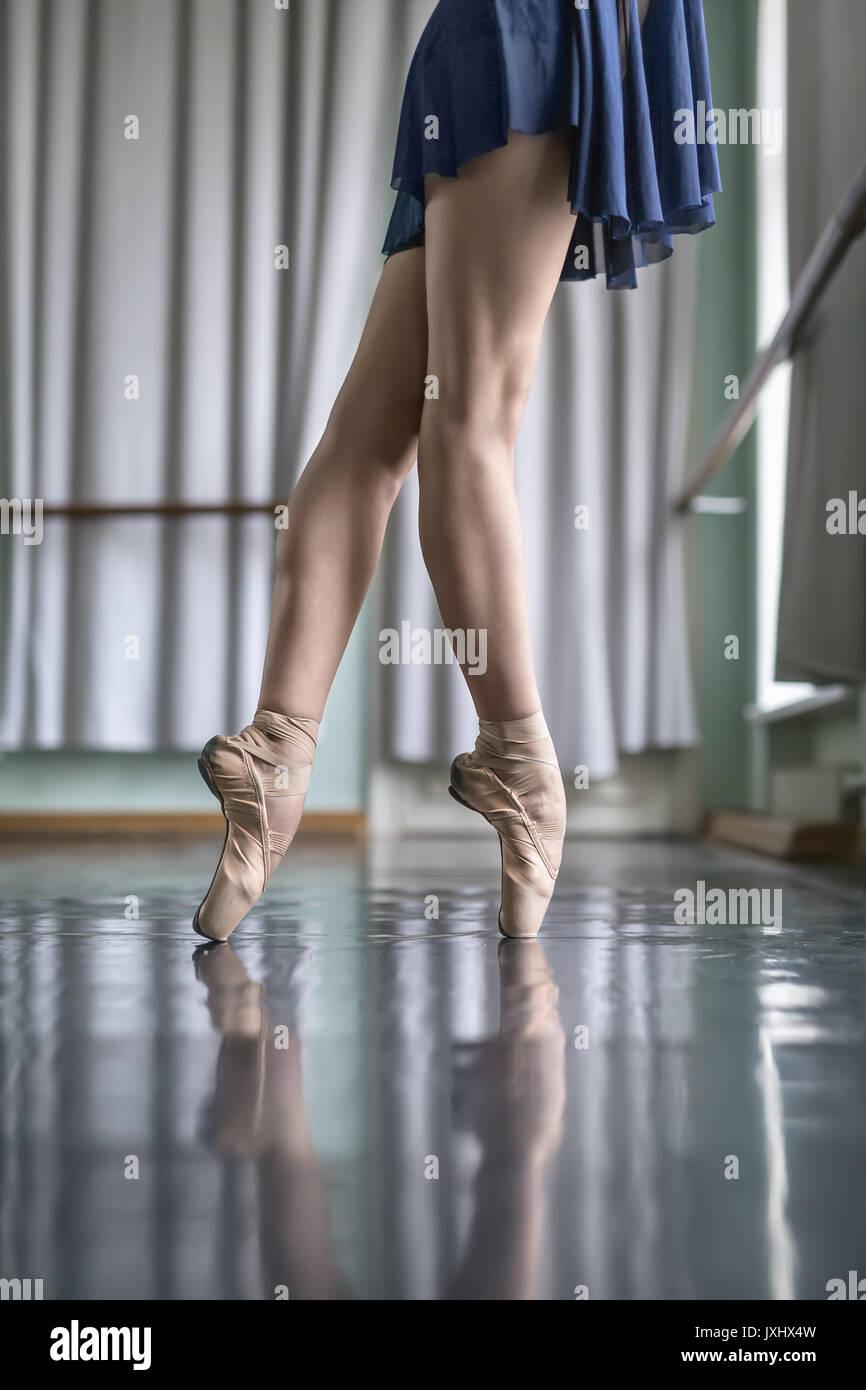 Le gambe della ballerina nella sala di balletto Immagini Stock