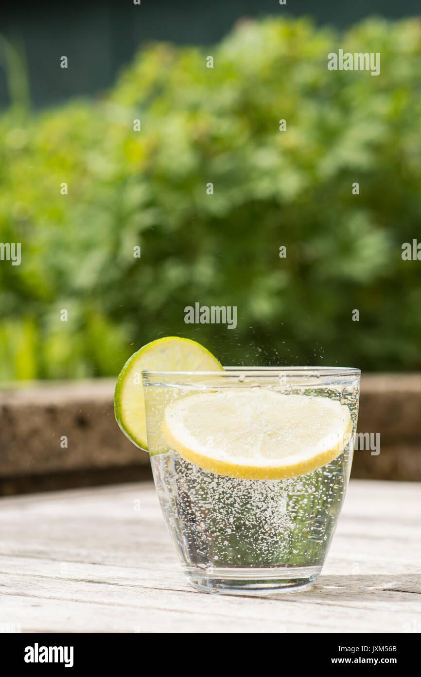 Bicchiere di gin tonic o la vodka e il tonico o acqua frizzante su una tavola di legno. Rinfrescante Immagini Stock