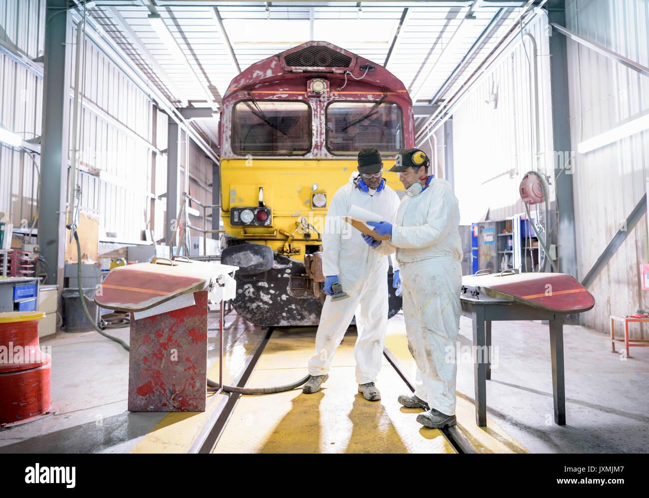 Pittori in paintshop con rinnovato locomotiva nel treno funziona Immagini Stock