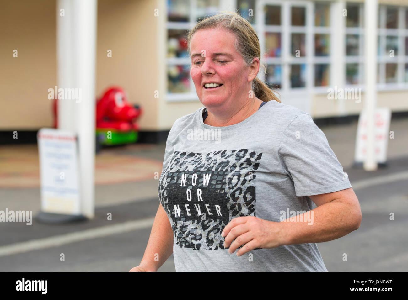Di mezza età Donna sovrappeso in esecuzione come parte del piano per perdere peso e per ottenere la misura, a Worthing vitalità Parkrun evento. Immagini Stock