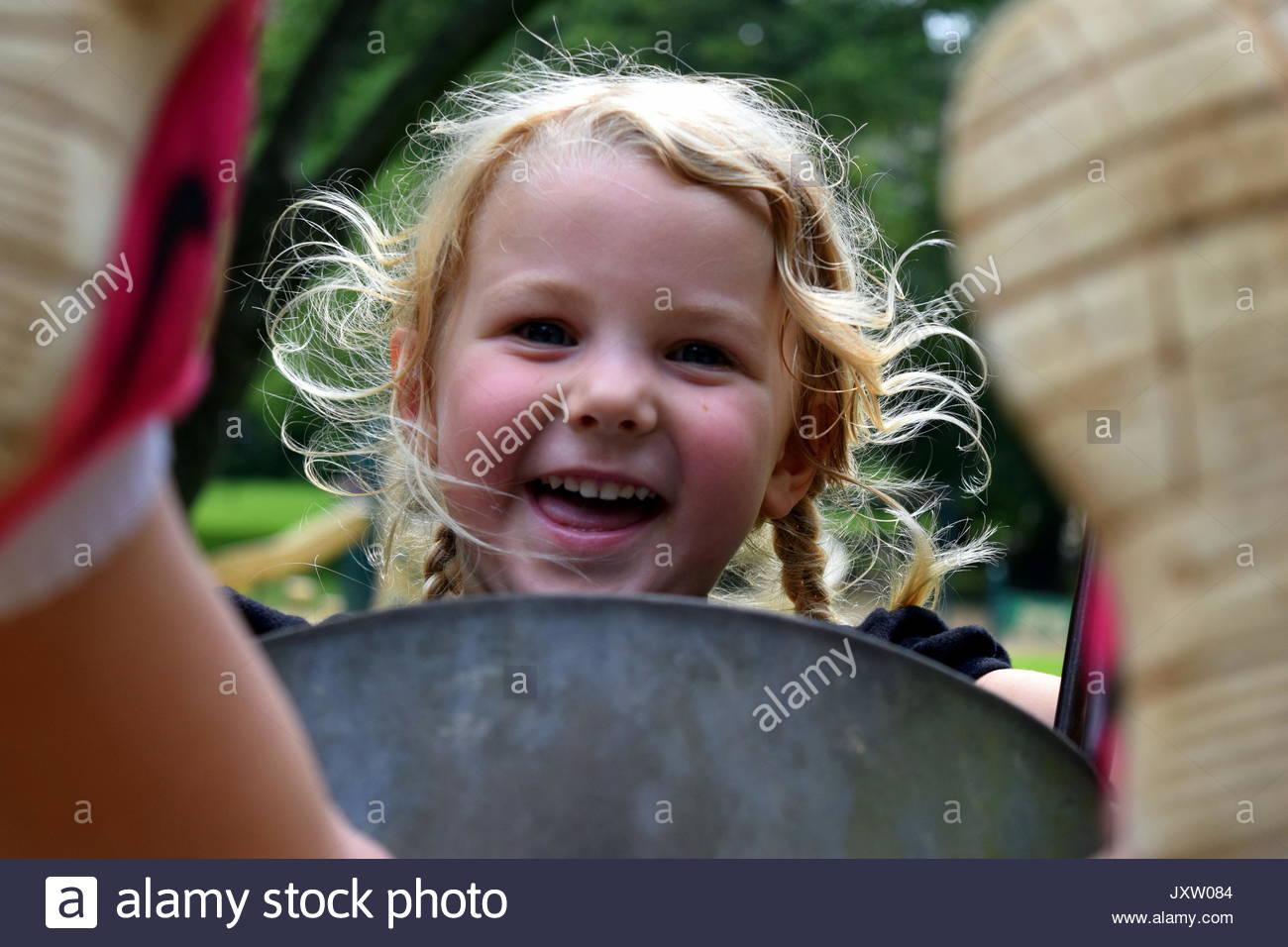 Sorridente ragazza in età prescolare oscillare in un parco Immagini Stock