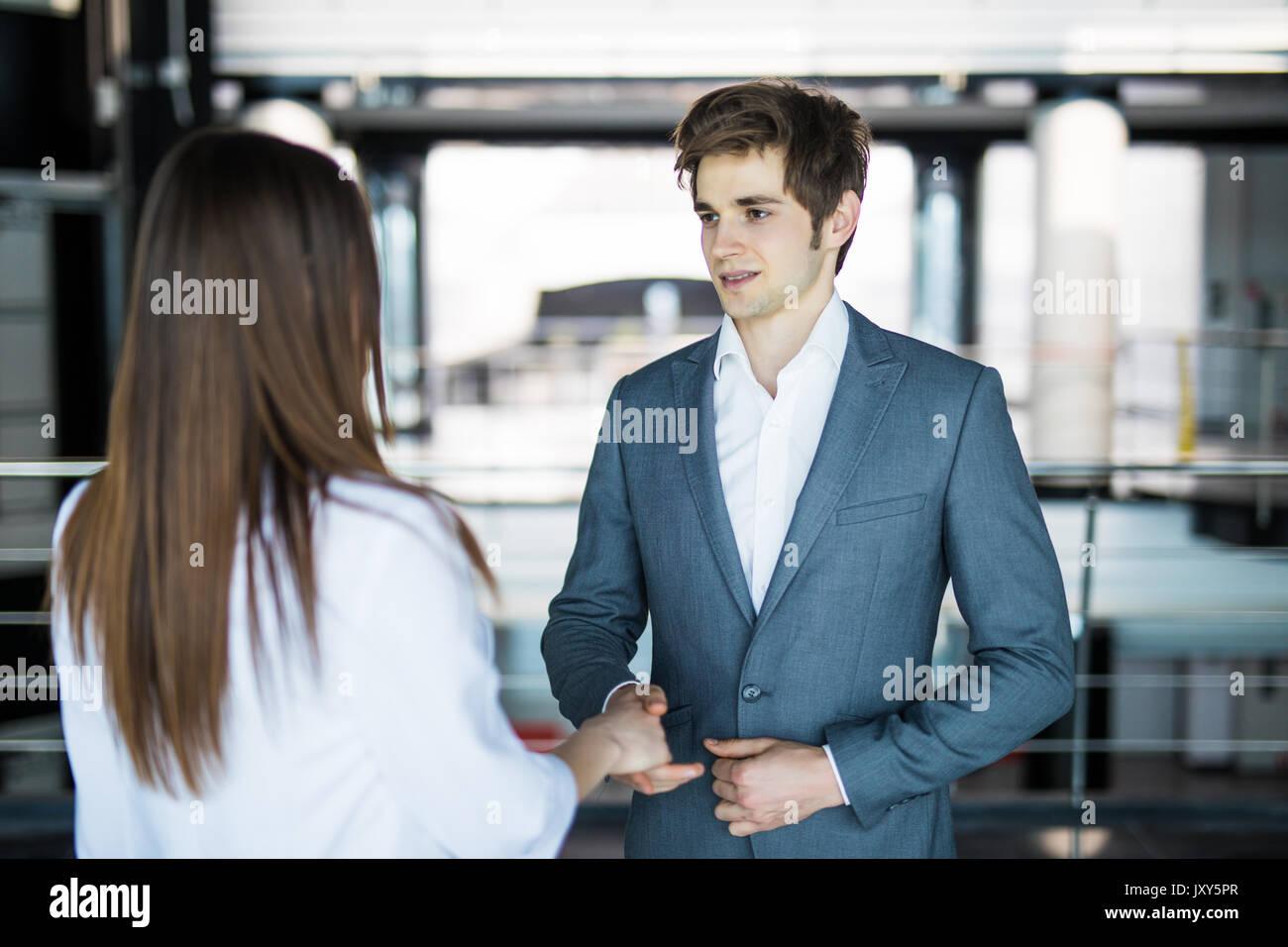 Uomini e donne di parlare con un sorriso sullo sfondo delle grandi finestre panoramiche in un moderno centro business. Immagini Stock