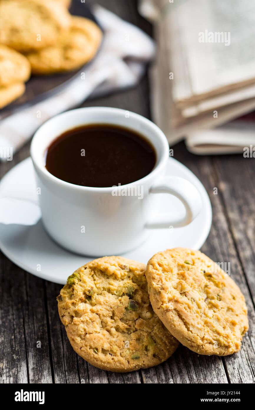 Dolce di pistacchio Biscotti e tazza da caffè sul vecchio tavolo in legno. Immagini Stock