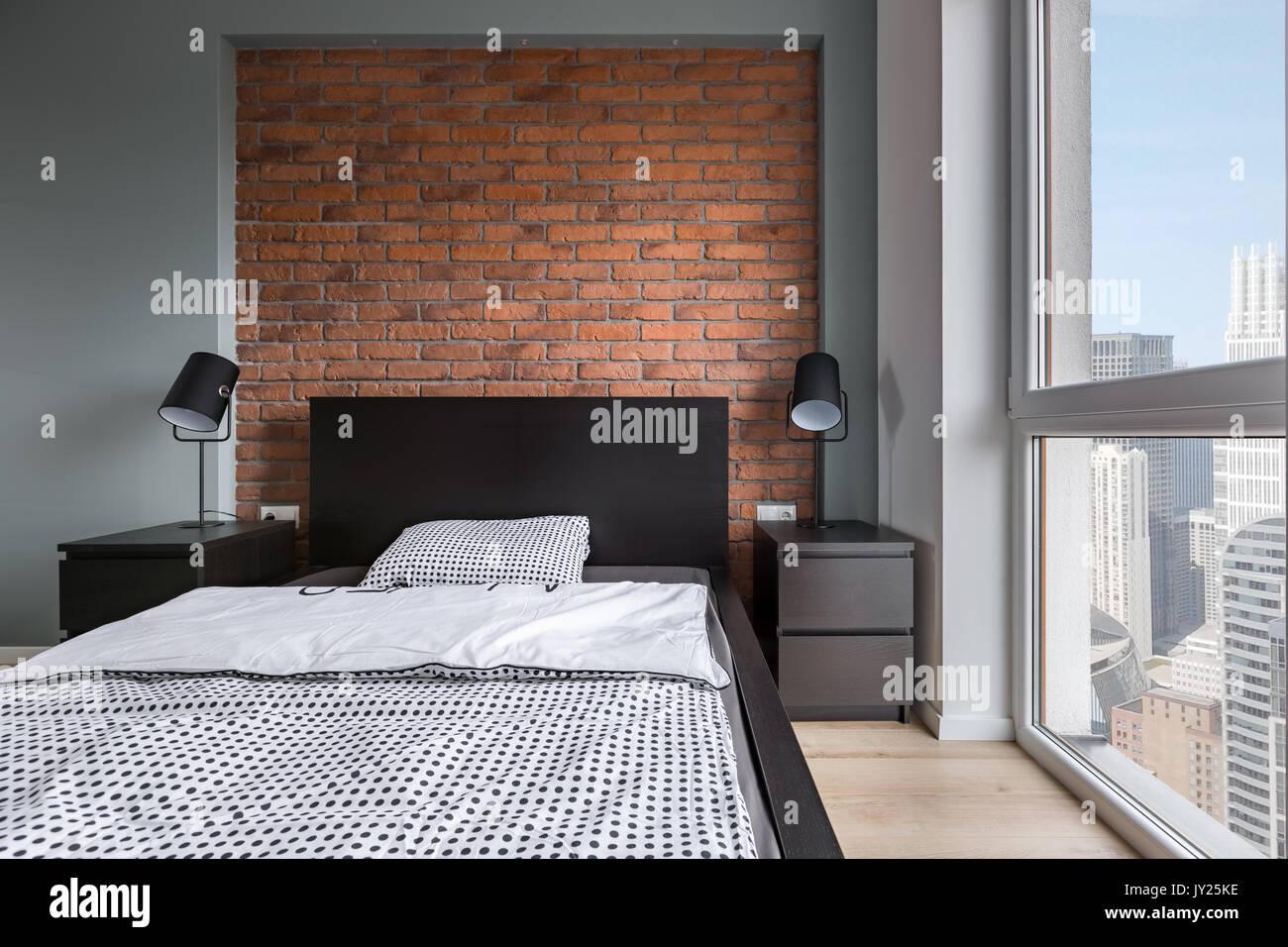 Semplice camera da letto con letto doppio muro di mattoni e una grande finestra foto immagine - Camera da letto grande ...