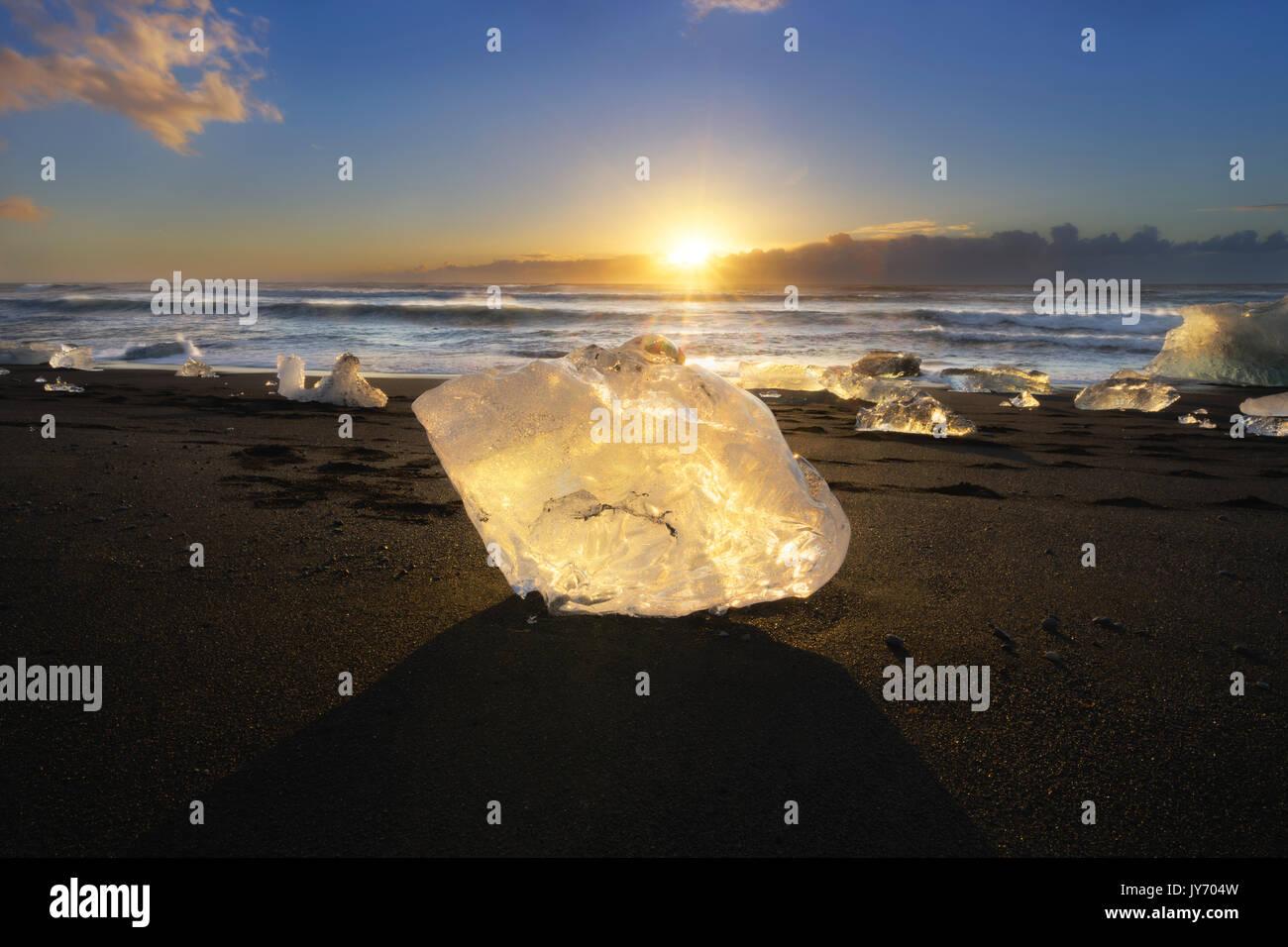 Blocco di ghiaccio sulla spiaggia nera di Jokulsarlon laguna glaciale di sunrise, Islanda Orientale, Europa Foto Stock