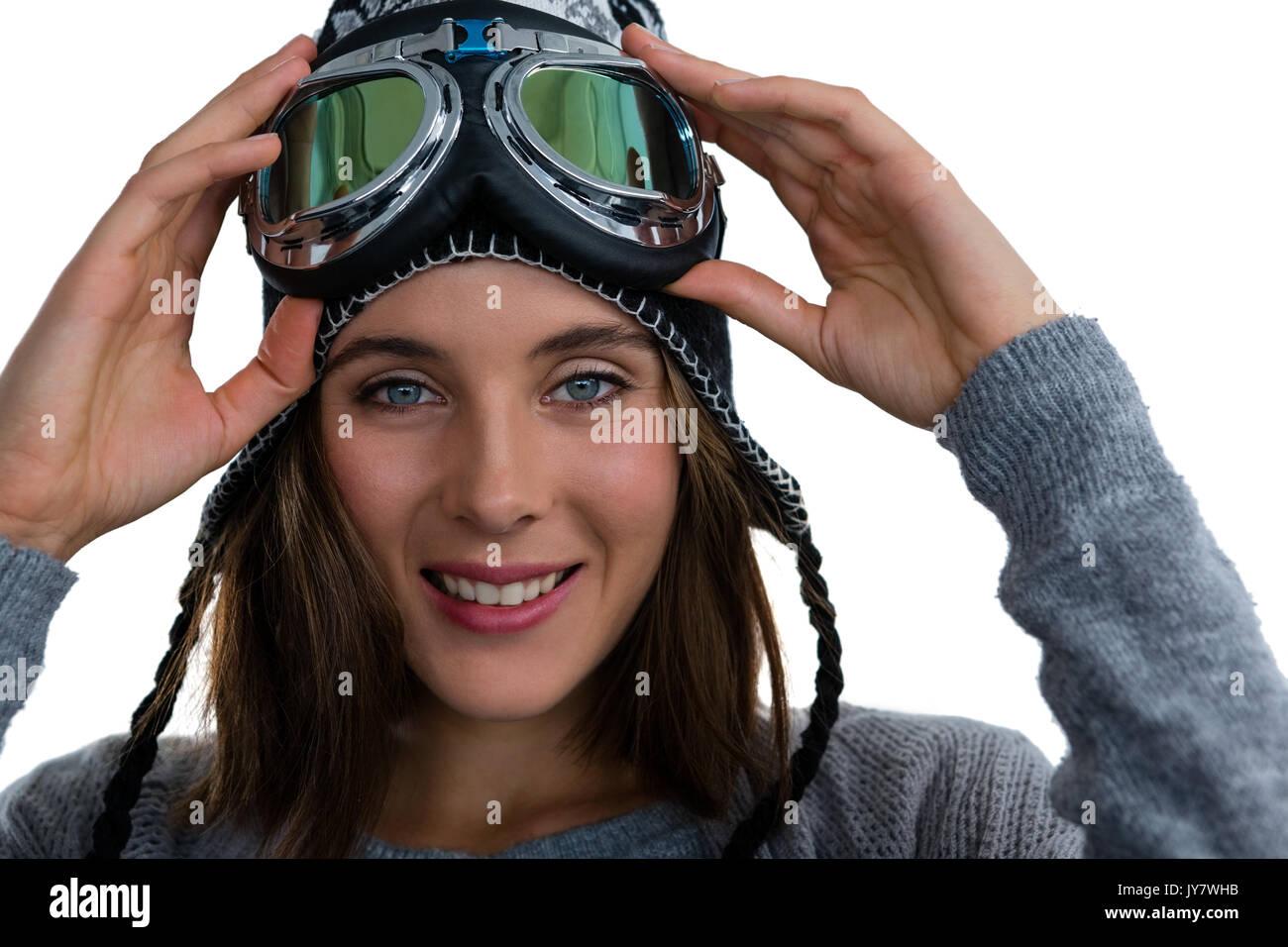 Ritratto di donna sorridente holding con maschere da sci contro uno sfondo bianco Immagini Stock