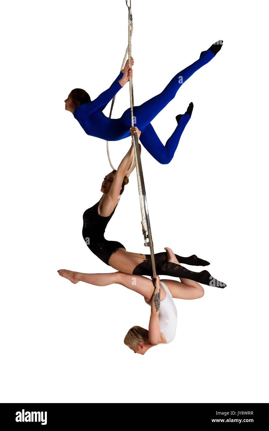 Giovane donna di trio facendo som acrobatici volteggi sull'antenna di lucentezza Immagini Stock