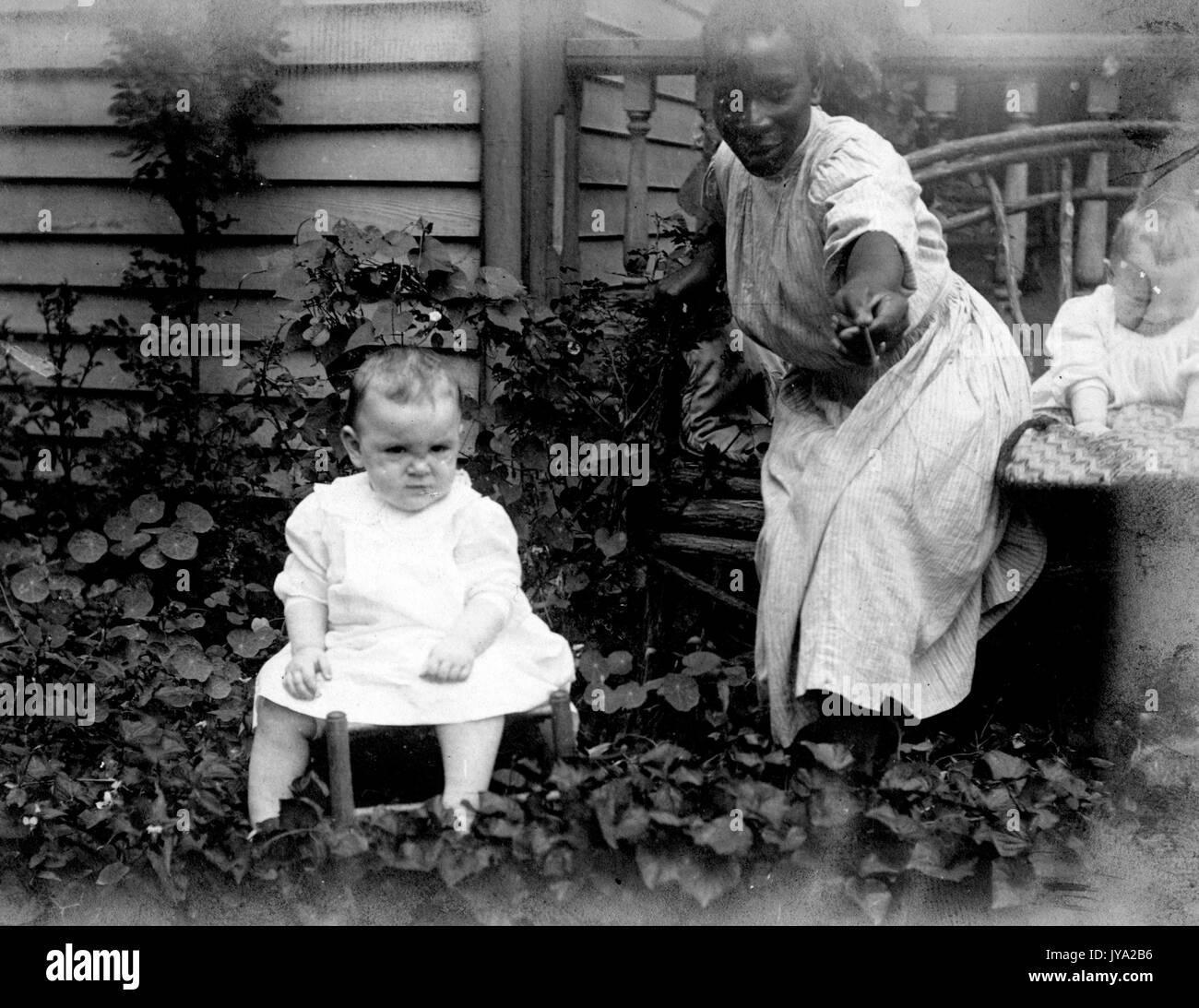 African-american bambinaia in un giardino accanto a una casa, indossando un abito semplice e tenendo fuori un fiore, con due giovani bambini caucasici, 1910. Immagini Stock