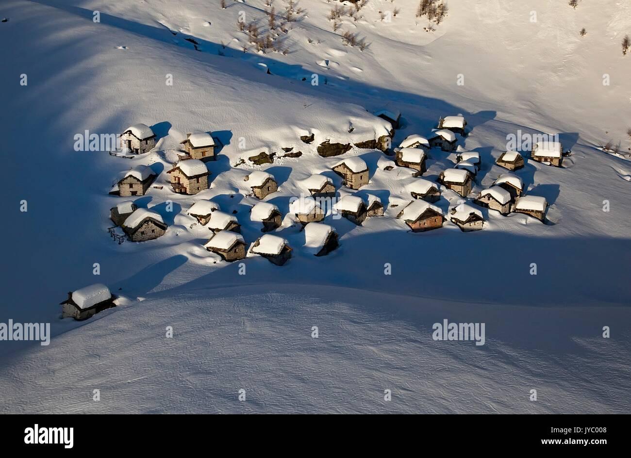 Vista aerea di rifugi di montagna di Lendine Alp dopo un pesante nevicata invernale. Valchiavenna. La Valtellina. Foto Stock