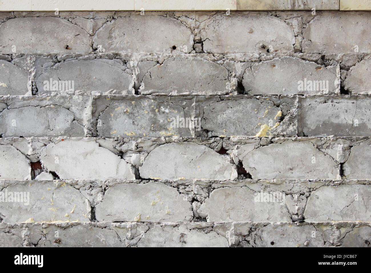 Grande Muro beige piastrelle è caduto, la consistenza del calcestruzzo di fondazione. Di lavoro difettoso. Immagini Stock