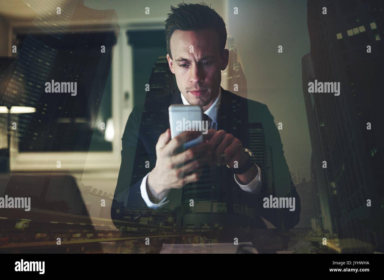 Il ragioniere intelligente seduto in ufficio e il surf lo smartphone durante la notte. Immagini Stock