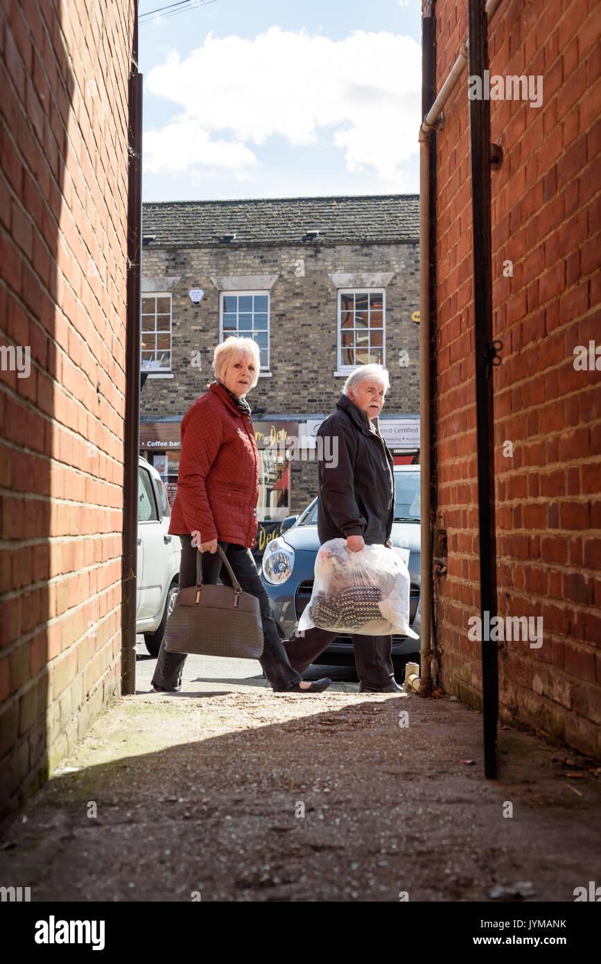 Gli anziani del peering giù un vicoletto oscurato in ombra lo sguardo direttamente verso il fotografo in condizioni di luce diurna su un tipico medio-alta-street in E Immagini Stock