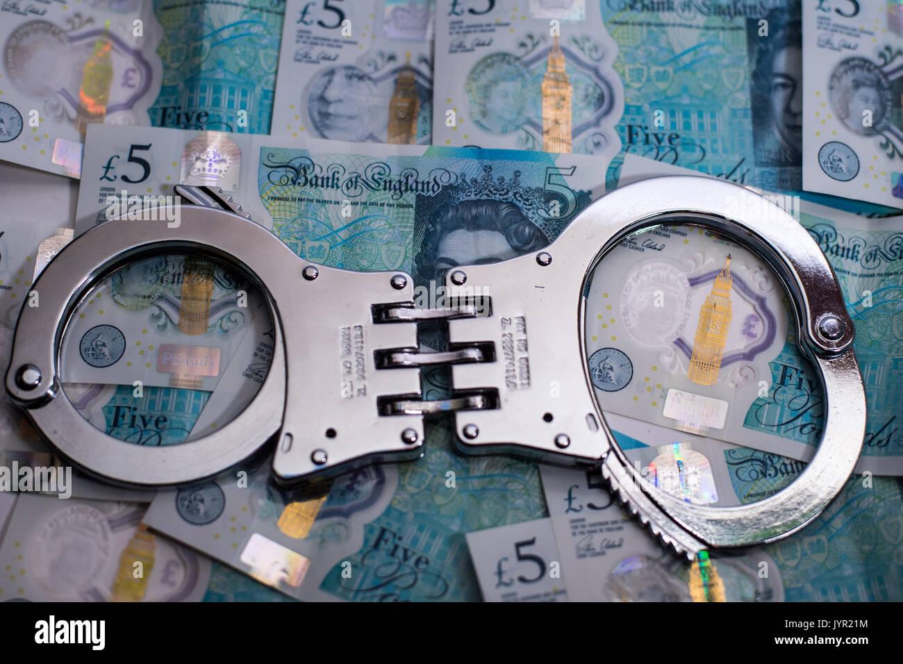 Manette sulla valuta £ 5 cinque pound note illustrante il fardello del debito Immagini Stock