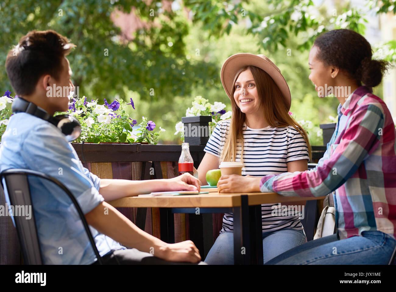 I giovani a parlare al tavolo del bar Foto Stock