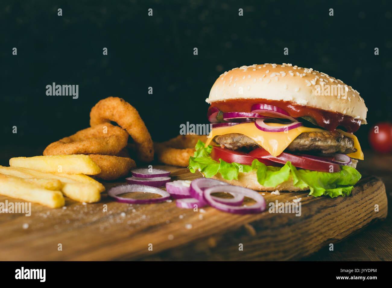 Cheeseburger, patatine fritte e anelli di cipolla sul tagliere di legno su sfondo di legno. Vista ingrandita, il fuoco selettivo. Il fast food concept Immagini Stock