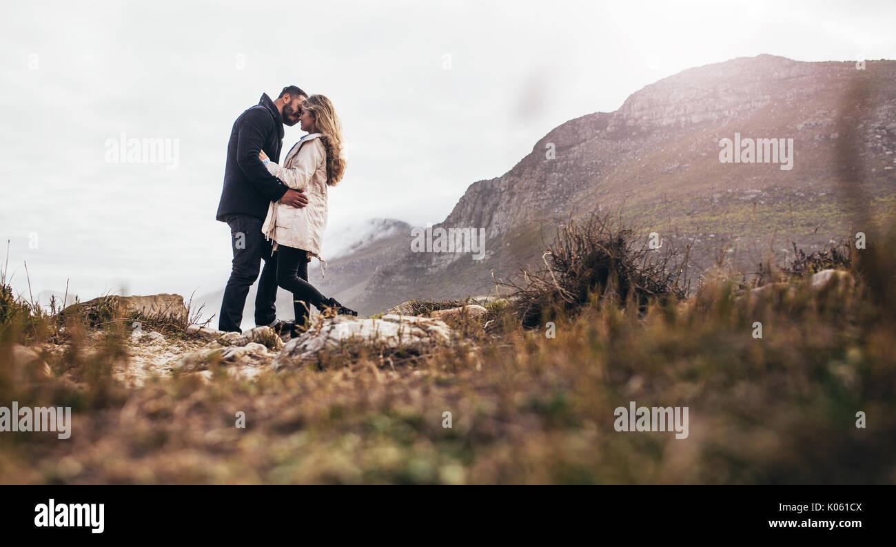 Coppia romantica baciare in natura. Inquadratura orizzontale di appassionato giovane sulla spiaggia durante le vacanze invernali. Immagini Stock