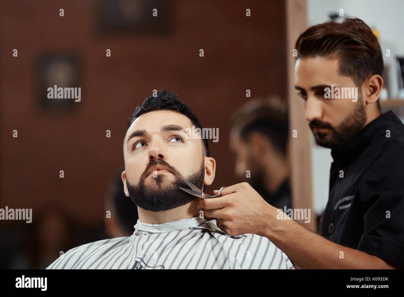 Barbiere barba di taglio con le forbici Immagini Stock