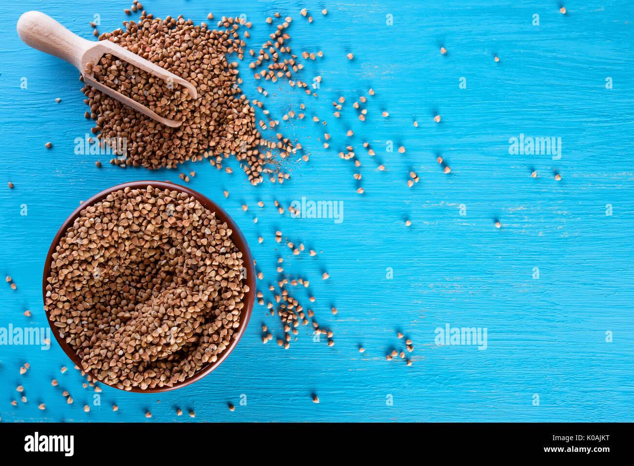 Ciotola di argilla con il grano saraceno groppa su uno sfondo blu Foto Stock