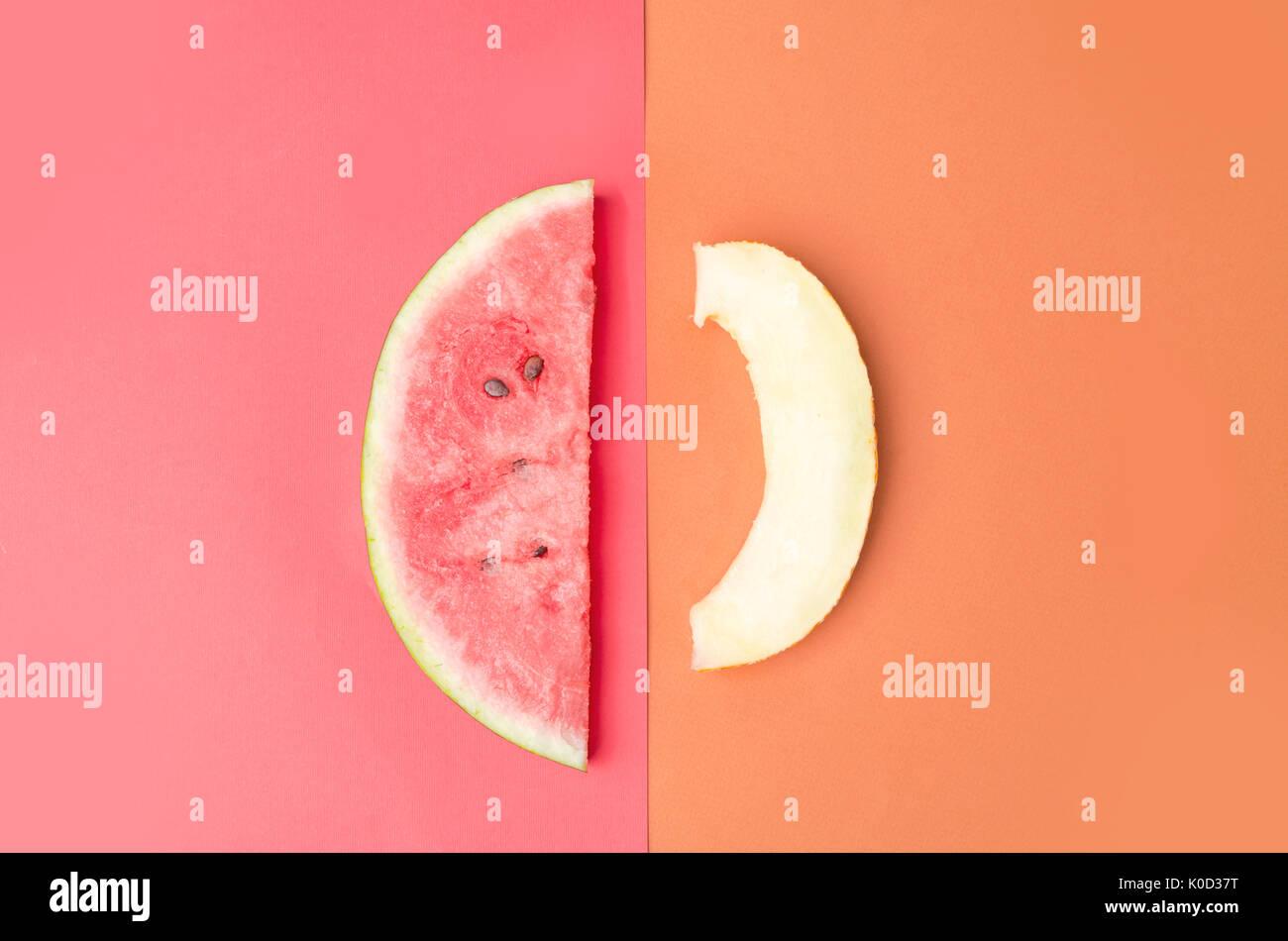 Fetta di anguria con pietre su sfondo rosso e melone isolate su sfondo arancione Immagini Stock