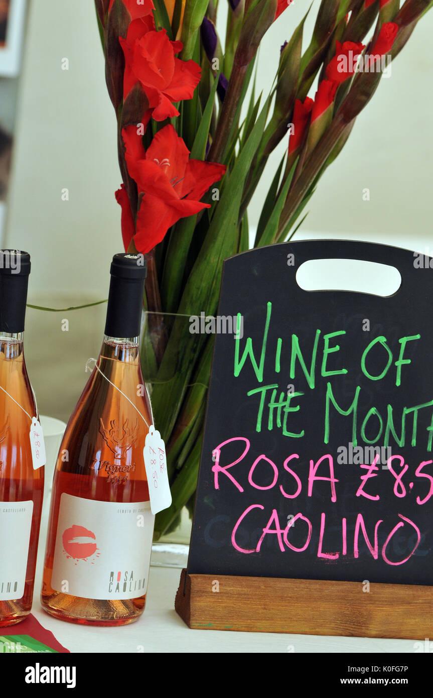 Due bottiglie di vini prodotti localmente in un mercato degli agricoltori con un segno che indica che questo è il vino del mese prossimo per alcuni fiori rossi in un vaso. Foto Stock