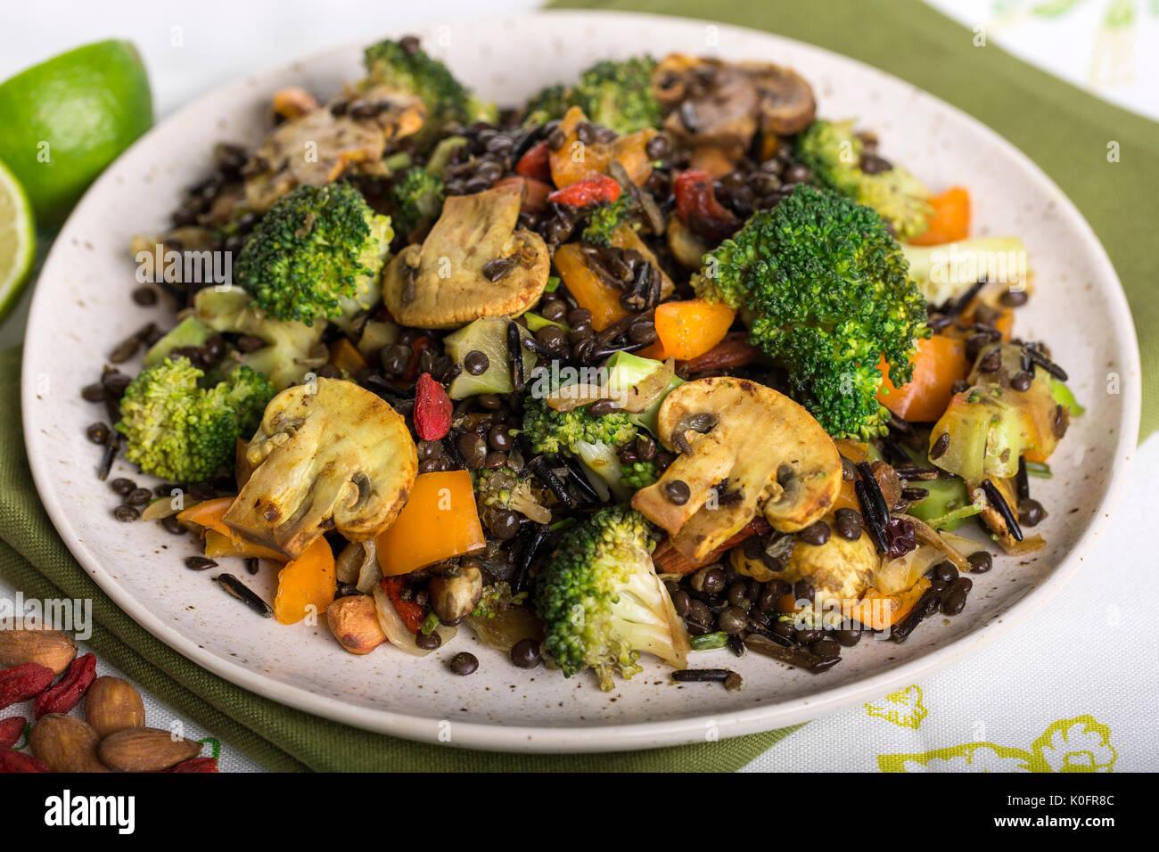 Closeup colpo di vegano sano mix di broccoli riso selvatico e piatto di lenticchie Immagini Stock