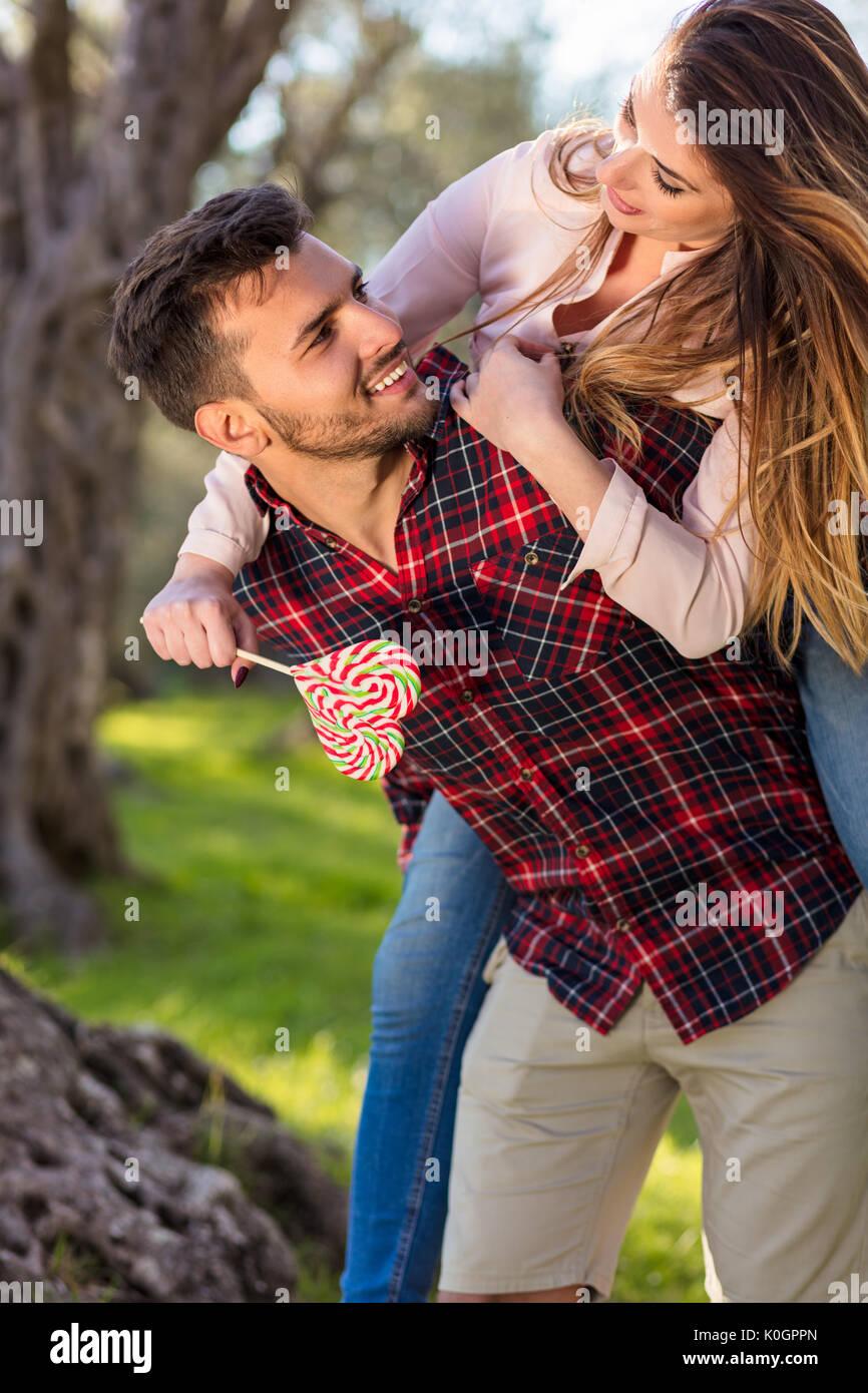 Ritratto di sorridere uomo bello dando piggy back per la sua fidanzata nella natura Immagini Stock