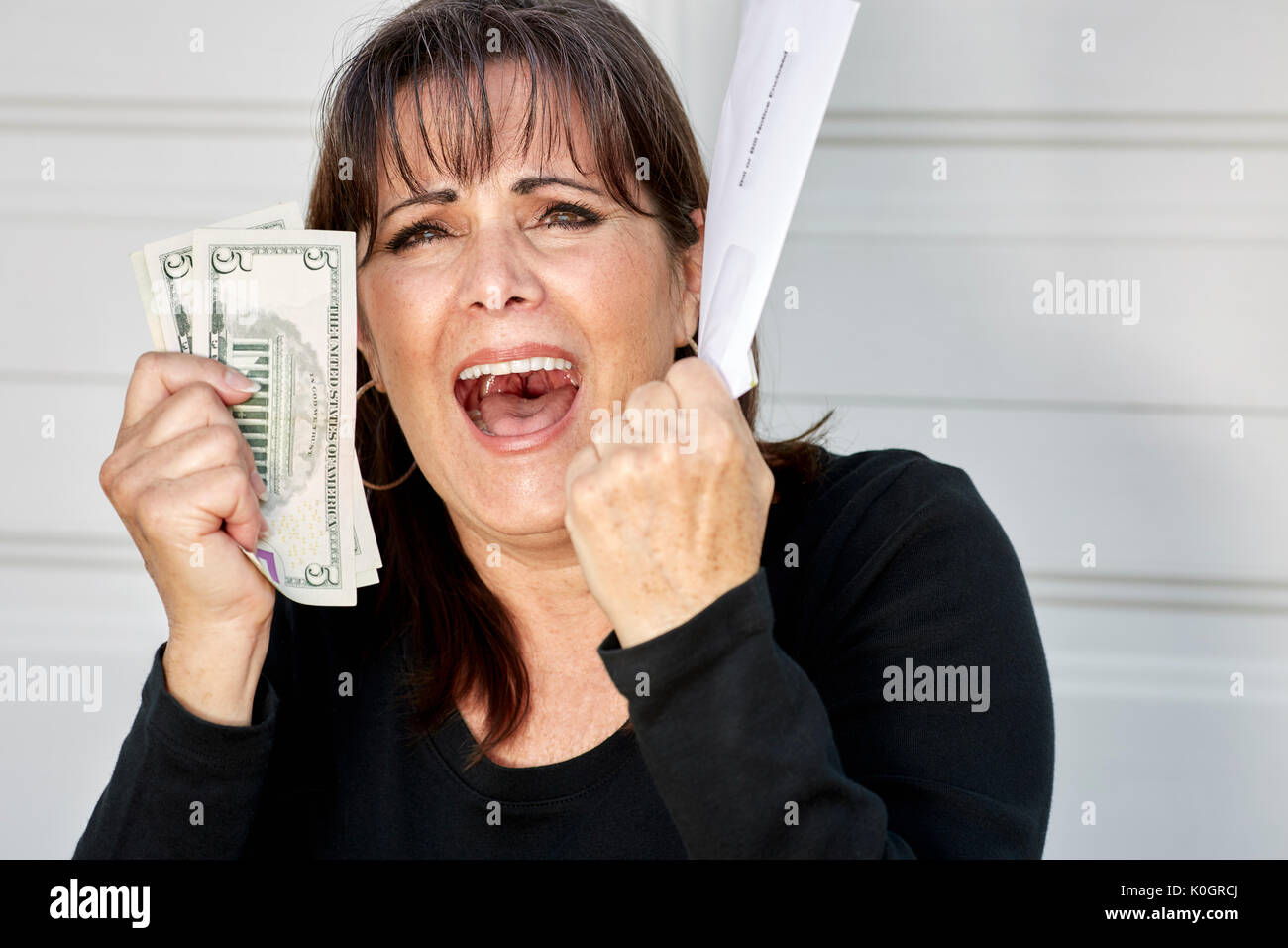 Una donna di mezza età tenendo le dichiarazioni delle fatture dovuto e valuta statunitense con un sconvolto, urlando espressione Immagini Stock