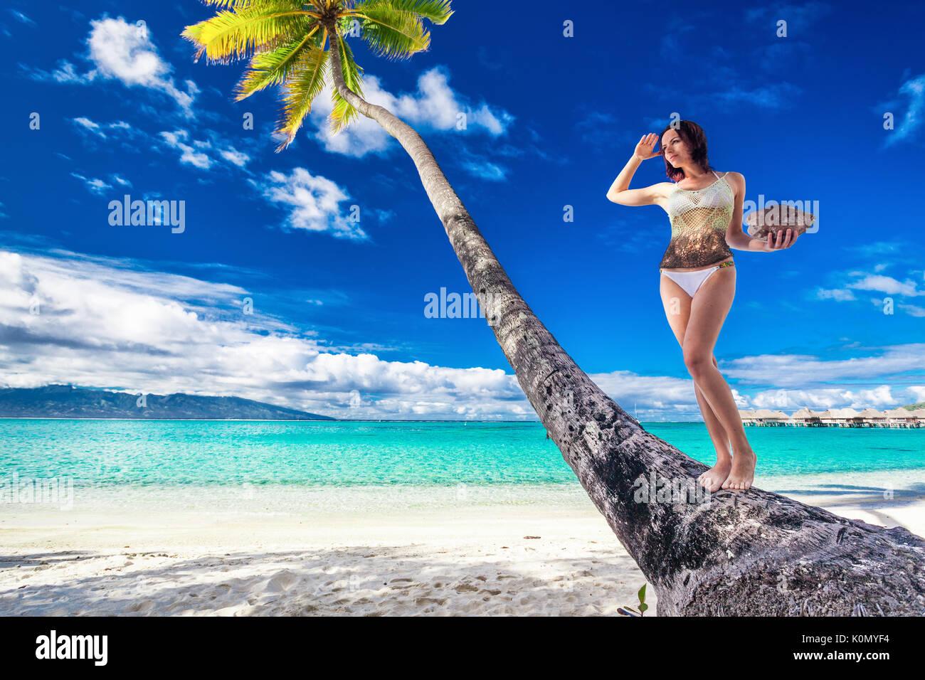 Giovane bella ragazza in bikini con noce di cocco sul palm tree su una spiaggia tropicale Immagini Stock