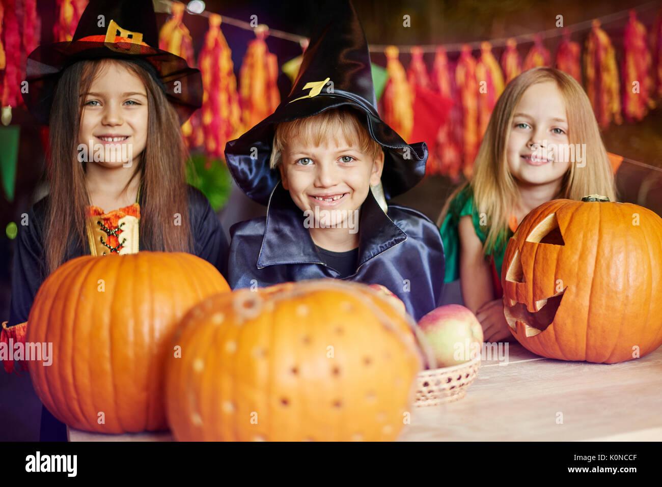 I bambini hanno un grande divertimento di intagliare le zucche Immagini Stock