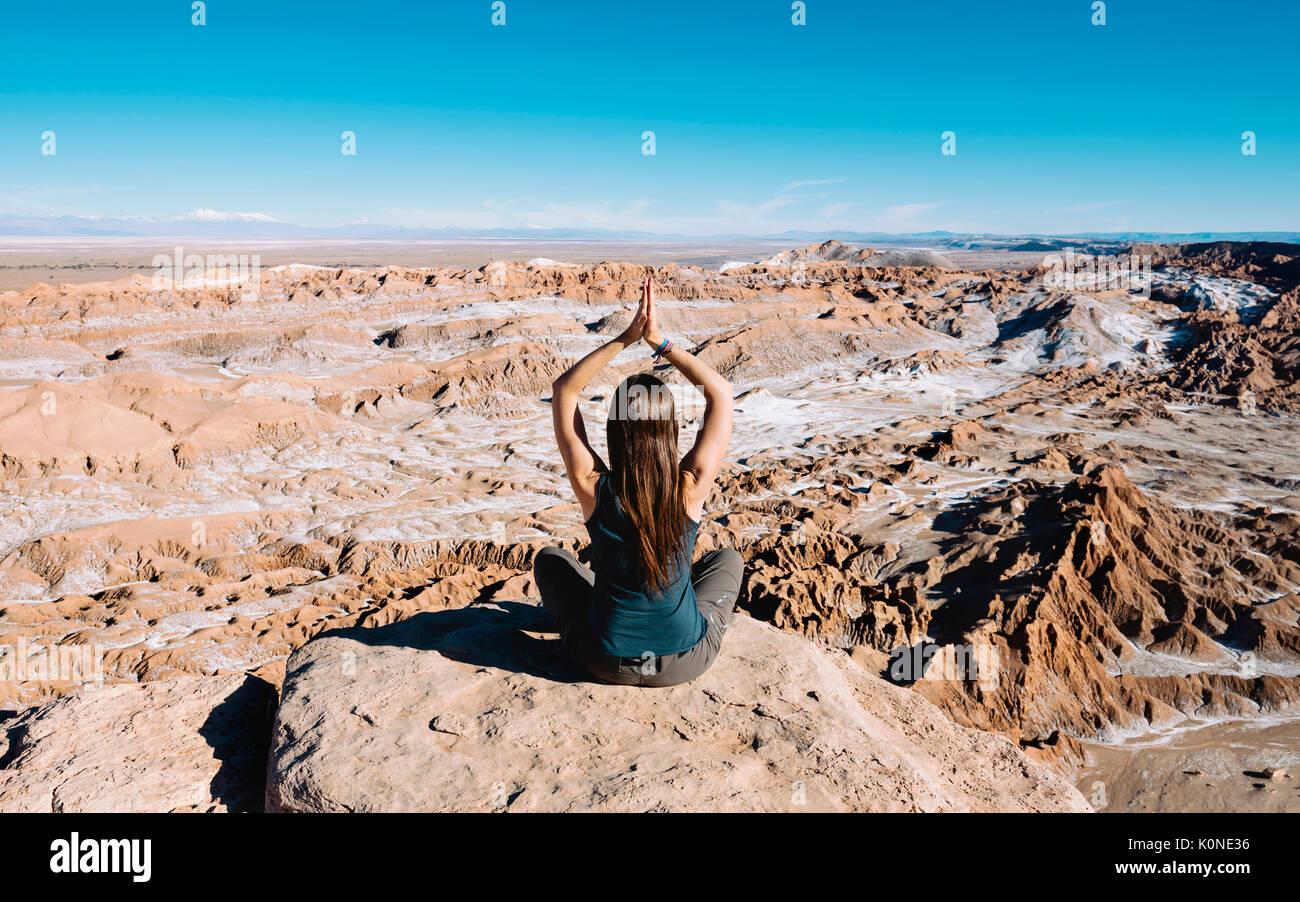 Il Cile, il deserto di Atacama, vista posteriore della donna a praticare yoga su una roccia Immagini Stock