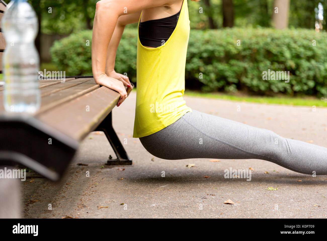 Sano giovane donna stretching prima di fitness e di esercizio nel parco, uno stile di vita sano concetto Immagini Stock