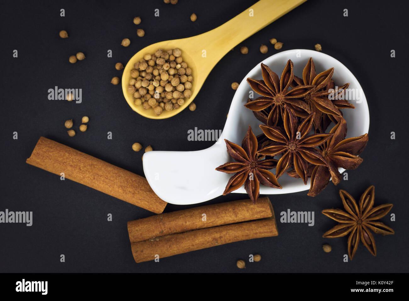 Anice stellato e spezie semi di coriandolo, semi di cumino, cannella su sfondo nero con spazio di copia Immagini Stock