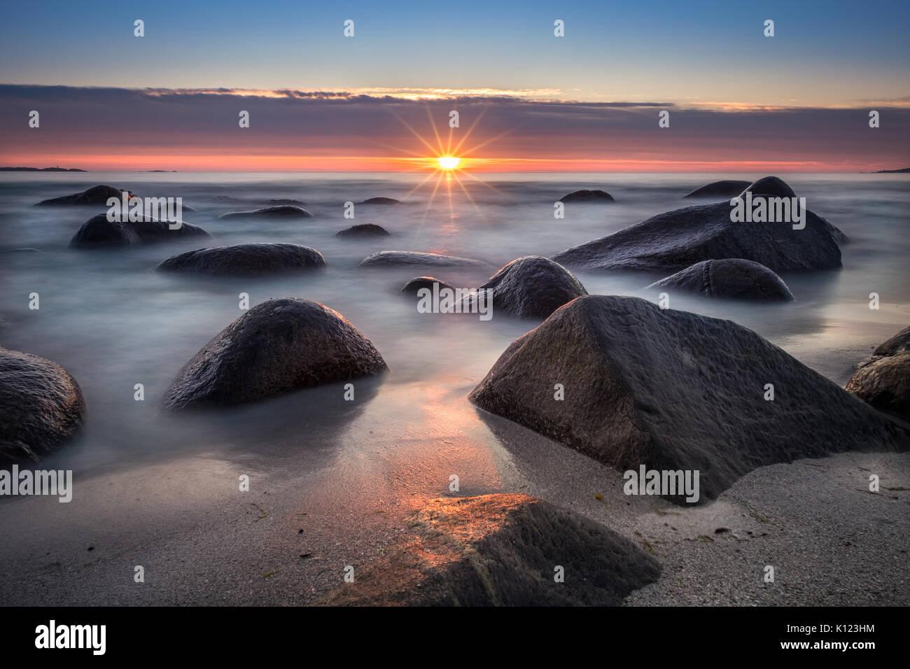 Vista panoramica dalla spiaggia con pietre e tramonto a notte estiva in Lofoten, Norvegia Immagini Stock