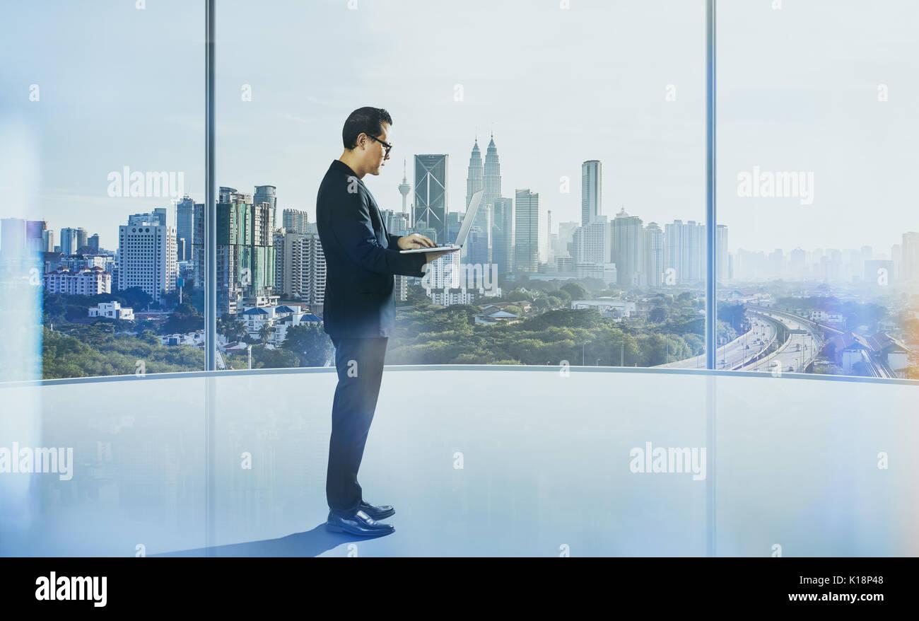 Uomo d affari con computer portatile con ufficio generico sfondo , scena notturna . Immagini Stock