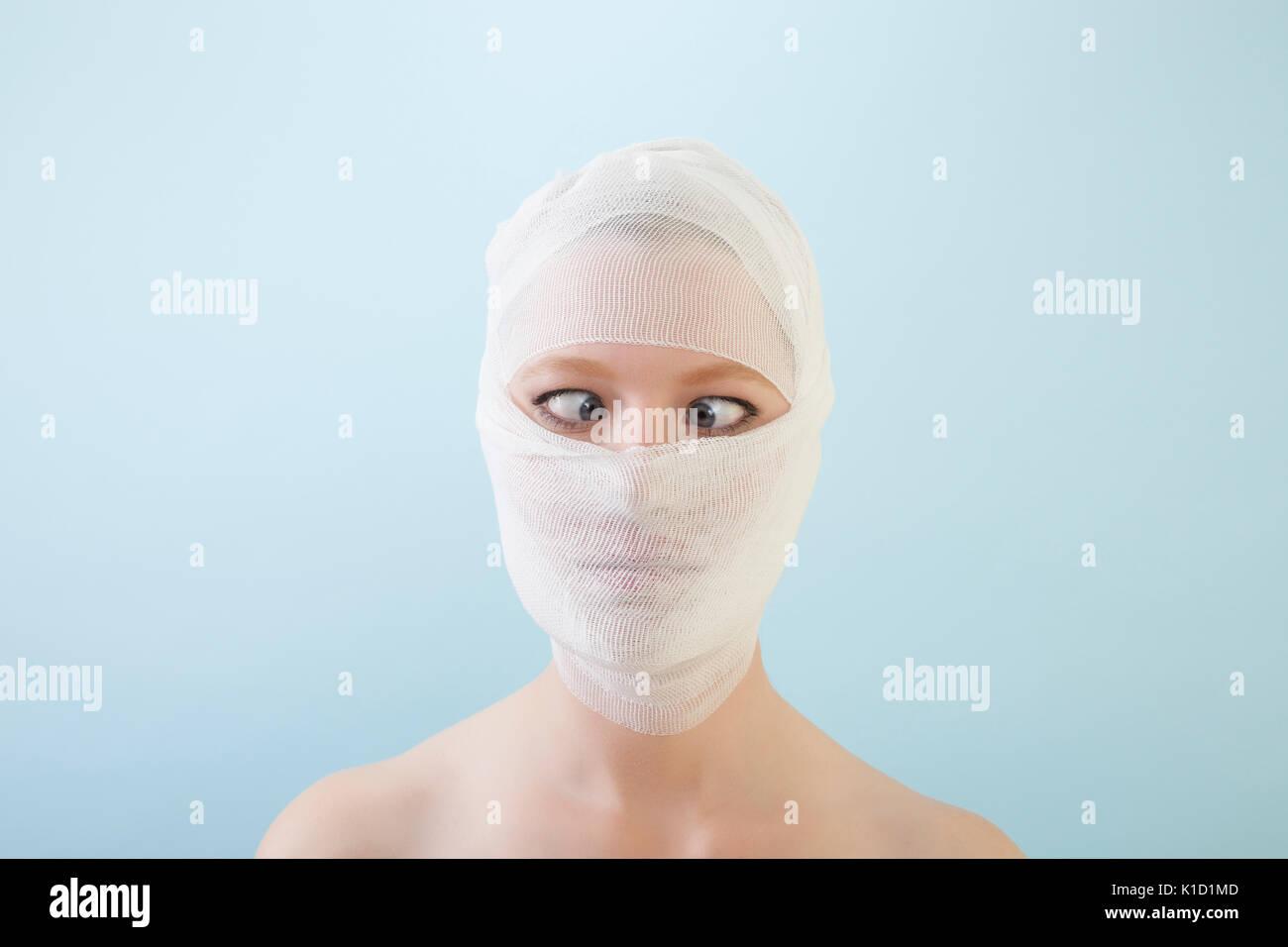 Giovani femmine è di guardare con i suoi occhi incrociati per la fotocamera dopo il suo intervento di chirurgia plastica con bende in tutto il suo volto. Contro lo sfondo blu. Immagini Stock