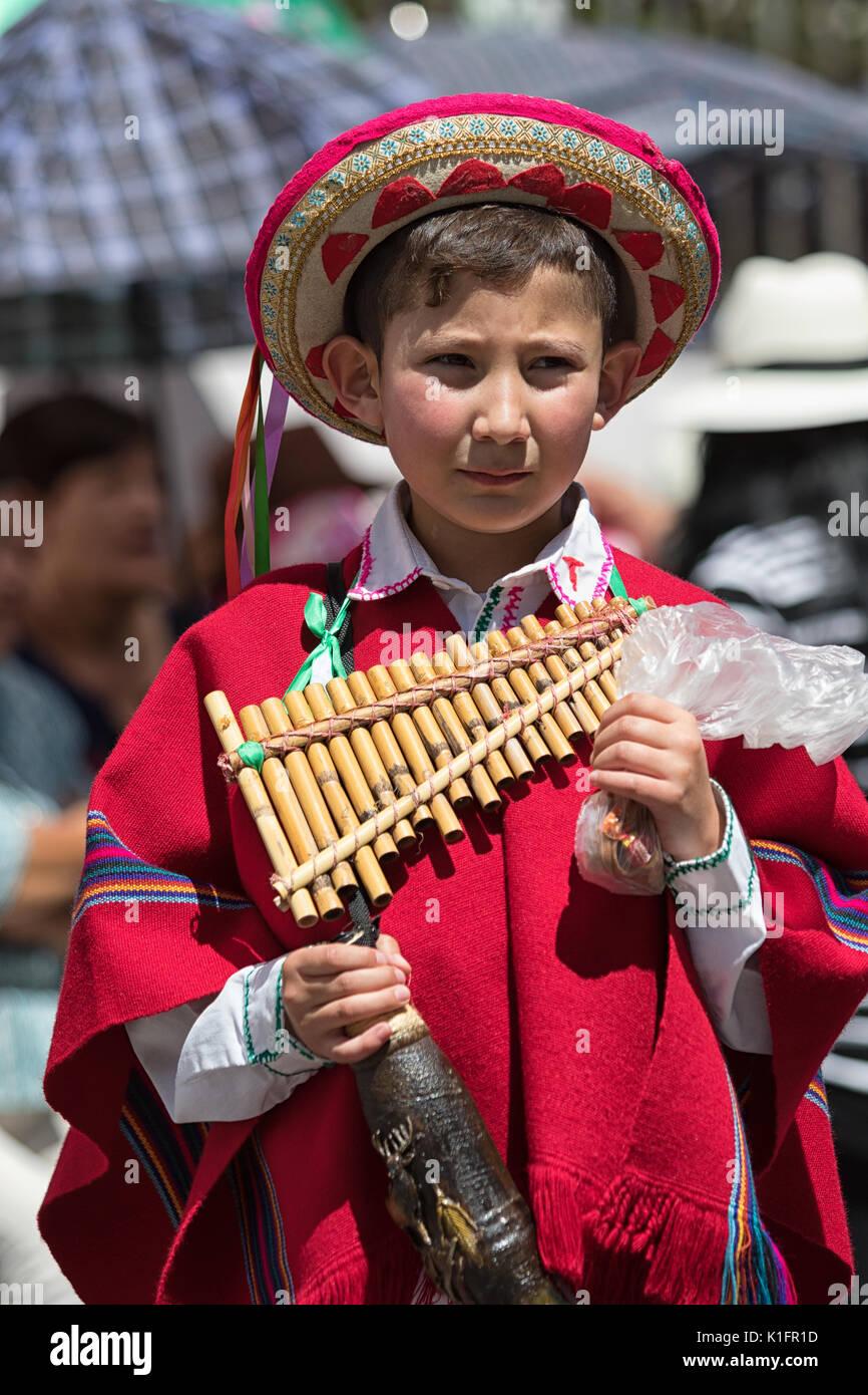 Giugno 17, 2017 Pujili, Ecuador: giovane ragazzo in abbigliamento tradizionale presso il Corpus Christi parade tenendo un flauto di pan Immagini Stock