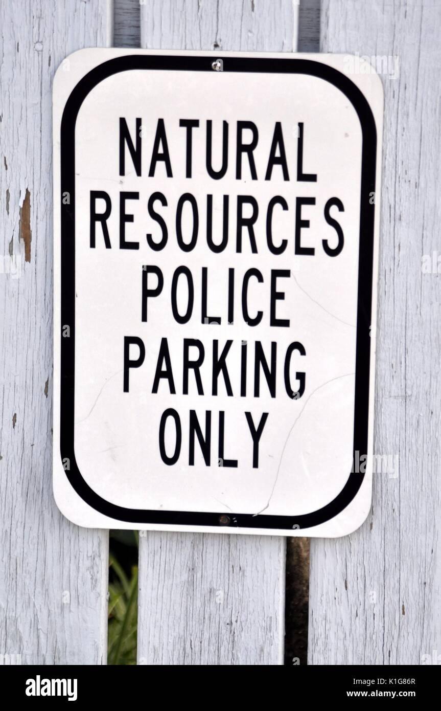 In bianco e nero delle risorse naturali parcheggio polizia solo segno contro un recinto grigio. Immagini Stock
